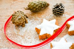 Christmas cookies. Pinecones and  red ribbon and sugar  on vintage wood background - dark moody image of decorative food, simple composition Royalty Free Stock Photo