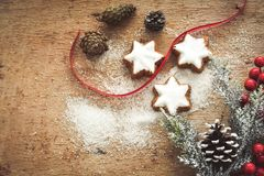 Christmas cookies. Pinecones and  red ribbon and sugar  on vintage wood background - dark moody image of decorative food, simple composition Stock Photo