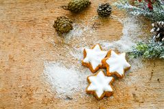 Christmas cookies. Pinecones and sugar  on vintage wood background - dark moody image of decorative food, simple composition Royalty Free Stock Photography
