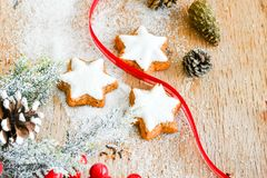 Christmas cookies. And red ribbon and sugar on vintage wood background - dark moody image of decorative food, simple composition royalty free stock images
