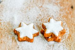 Christmas cookies. Christmas star  cookies and snow from  sugar on vintage wood background - dark moody image of decorative food, simple composition. Card Royalty Free Stock Photos