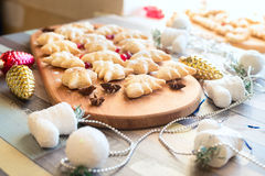 Christmas cookies among Christmas-tree decorations, toys, spices. And cranberries lies on the old wooden table. Close up Royalty Free Stock Images
