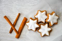 Christmas cookies. And cinnamon on vintage wood background - moody of decorative food, simple composition royalty free stock photos