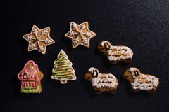 Christmas cookies. Colorful christmas biscuits decorated with sugar on black royalty free stock image