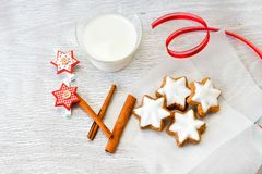 Christmas cookies. Cup of milk , cinnamon and red dibbon on vintage wood background - dark moody of decorative food, simple composition stock images