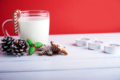 Christmas cookies with cup of milk at a red background Stock Photos