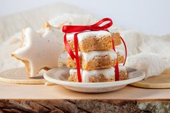 Christmas cookies decorated on wooden background with napkin. And red ribbon, German Zimtsterne Stock Photo