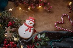 Christmas cookies and festive decor. Christmas cookie snowman and festive decor at wooden background with place for text stock images