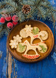 Christmas cookies in festive decoration. Christmas cookies in festive decor on wooden plate and blue rustic table decorated with fir branches Royalty Free Stock Photo