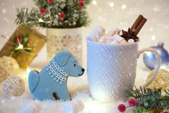 Christmas cookies with festive decoration in the shape of a dog and white cup of hot spicy Christmas drink. Royalty Free Stock Image