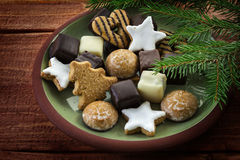 Christmas cookies and fir branches, plate full of traditional gi Royalty Free Stock Image