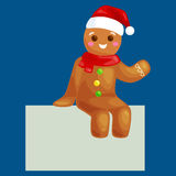 Christmas cookies gingerbread man decorated with icing sitting on a plate in a Christmas hat and scarf, xmas sweet food Stock Image