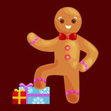 Christmas cookies gingerbread man decorated with icing standing on a stack of gifts Royalty Free Stock Photo
