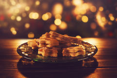 Christmas cookies on a glass plate. Jam filled Christmas cookies on a glass plate in low golden light with some bokeh in background Stock Photo