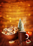 Christmas cookies. Image of Xmas sweets, traditional Christmastime gingerbread with candy cane on festive table, coffee cup decorated with little decorative stock image