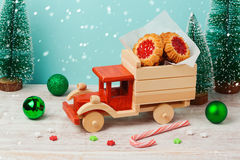 Christmas cookies with jam in toy truck on wooden table stock photo