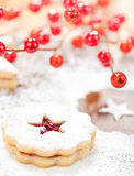 Christmas Cookies. Christmas Linzer cookie with powdered icing sugar and red decorations in the background royalty free stock photography
