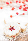 Christmas Cookies. Christmas Linzer cookie with powdered icing sugar and red decorations in the background royalty free stock image