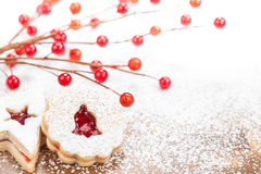 Christmas Cookies. Christmas Linzer cookies decorated with powdered icing sugar and red decorations in the background. Copy Space royalty free stock image