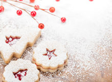 Christmas Cookies. Christmas Linzer cookies decorated with powdered icing sugar and red decorations in the background. Copy Space stock photos