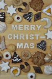 Christmas cookies and MERRY CHRISTMAS. Different kinds of Christmas cookies on a breadboard around the words: MERRY CHRISTMAS Royalty Free Stock Photography
