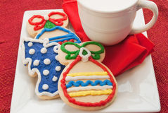 Christmas Cookies and Milk. Homemade Christmas cookies served with a cup of milk. Square dish with red napkin and place mat. Shot in Royalty Free Stock Photography