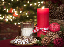 Christmas Cookies and Milk Waiting for Santa Claus in Candle Light with a Lighted Christmas Tree in background on Christmas Eve Stock Photos
