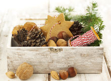 Christmas cookies, nuts and pine cones in wooden box. Royalty Free Stock Photos