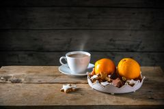 Christmas cookies and oranges in a bowl and a cup with hot coffee on a rustic table, dark wooden background with a large copy spa stock photos