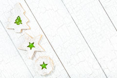 Christmas cookies. Overhead view of 3 Christmas linzer cookies with green jelly arranged diagonally on white painted background. Copy Space stock images