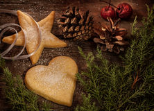 Christmas cookies, pine tree branch and pinecones on wood Stock Images
