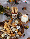 Christmas cookies on a plate decorated on a table and white lighted candle Royalty Free Stock Photo