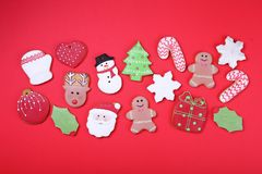 Christmas cookies on red background top view. Various types christmas gingerbread cookies flat lay. Christmas characters cookies. Royalty Free Stock Image