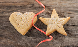 Christmas cookies and red ribbon on vintage wood background. Decorative food, simple composition Stock Photography