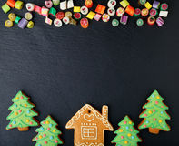 Christmas cookies in the shape of house and new year tree, mixed candy. On slate Stock Images
