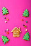 Christmas cookies in the shape of house and new year tree, mixed sweet candy. On pink background Stock Photo