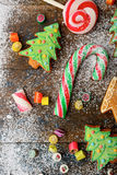 Christmas cookies in the shape of tree, cane and candy strewn with snow Royalty Free Stock Photos