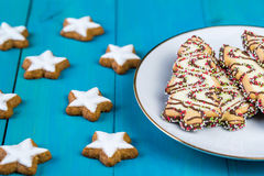 Christmas cookies in a shapes of stars and christmas trees on wooden background Stock Photos