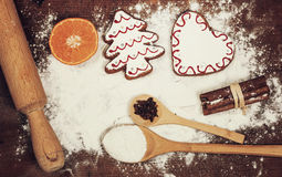Christmas cookies, spices and flour on wooden chopping board Royalty Free Stock Images