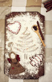 Christmas cookies, spices and flour on wooden chopping board Stock Images