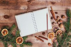 Christmas cookies, spices and recipe book. Food background. Vintage style picture. Christmas greeting card and food decor on brown wooden table with fir tree Stock Photo