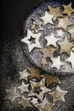 Christmas cookies sprinkled by sugar on the ceramic plate Stock Photos