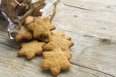 Christmas cookies in star shape falling from a cellophane bag on. A rustic wooden table, copy space Stock Image
