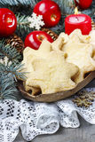 Christmas cookies in star shape, red apples and green fir Royalty Free Stock Photo