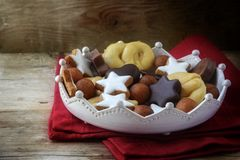 Christmas cookies and sweets like homemade cinnamon stars, marzipan balls, chocolate and biscuit in a pottery crown bowl on a red royalty free stock image