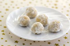 Christmas cookies, tasty balls with hazelnut inside and icing sugar, white plate and tablecloth with golden star. S royalty free stock image