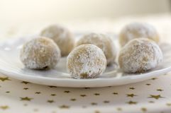 Christmas cookies, tasty balls with hazelnut inside and icing sugar, white plate and tablecloth with golden star. S royalty free stock images