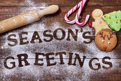 Christmas cookies and text seasons greetings. High-angle shot of a wooden table sprinkled with icing sugar or flour where you can read the text seasons greetings Stock Photo