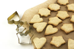 Christmas cookies and  tins baking on a baking paper Stock Photos