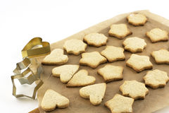 Christmas cookies and  tins baking on a baking paper Royalty Free Stock Photography
